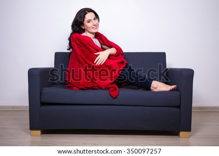 relaxation concept - young beautiful woman sitting on sofa wrapped in red blanket - stock photo
