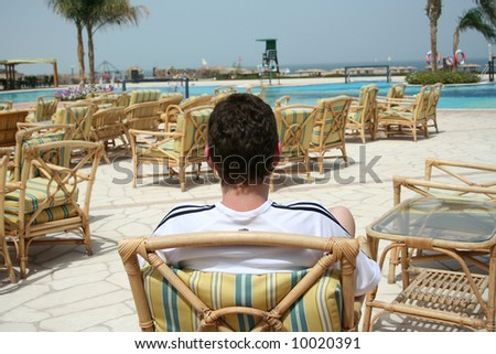 Relaxation in an armchair near pool - stock photo