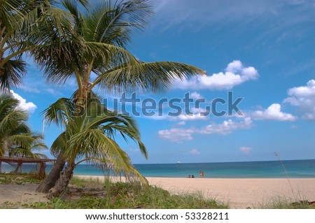 Relaxation on the beach under palm trees - stock photo