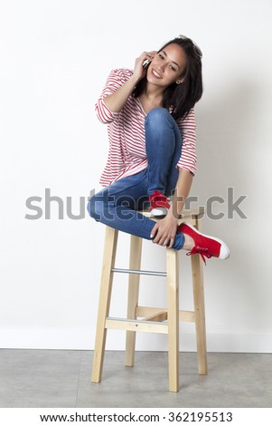 relaxation on the phone - relaxed 20s multi-ethnic girl smiling on her mobile phone, sitting on a stool to enjoy communication, white background - stock photo