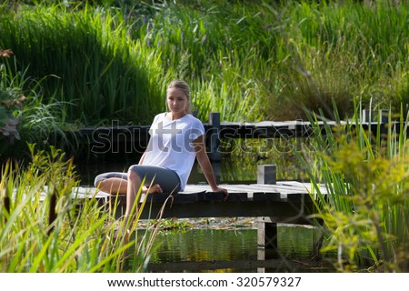 relaxation outside - daydreaming young woman enjoying putting her bare feet in water,sitting on a wooden bridge, green park environment, summer daylight - stock photo