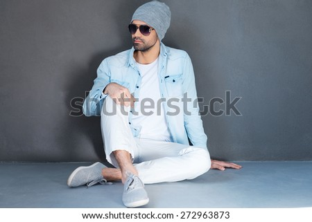 Relaxed and carefree. Handsome young man in eyewear sitting on the floor against grey background - stock photo