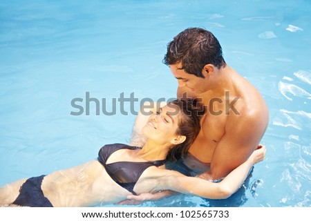 Relaxed attractive couple bathing together in swimming pool - stock photo