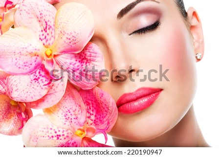 Relaxed beautiful face of a young girl with clear skin and pink orchids. Beauty treatment concept - stock photo