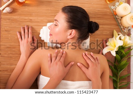 Relaxed beautiful young woman having a spa massage on her back - stock photo