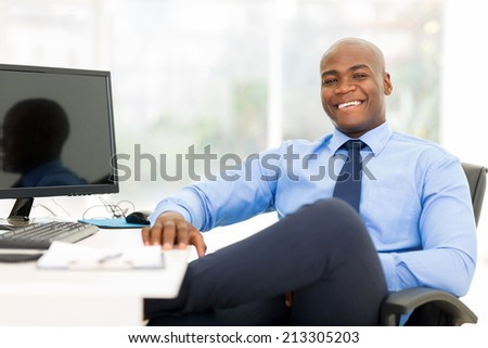 relaxed black businessman sitting in modern office - stock photo