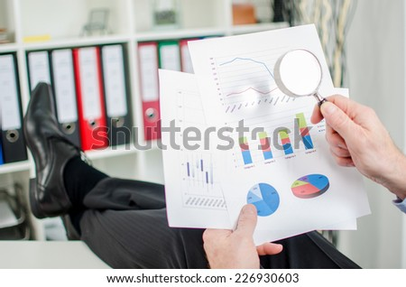 Relaxed businessman analyzing a financial graph with a magnifying glass - stock photo