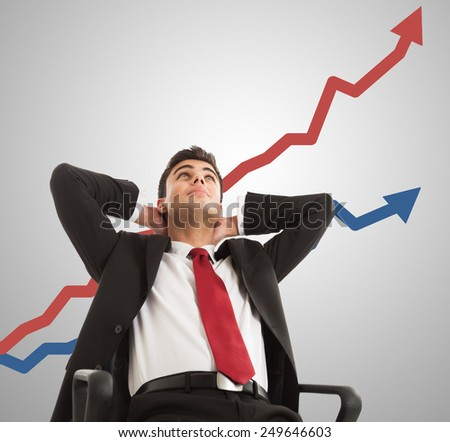 Relaxed businessman looking at a growing graph - stock photo