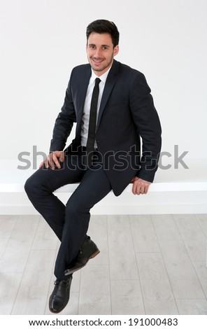 Relaxed businessman sitting on desk - stock photo