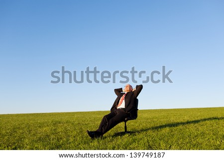 Relaxed businessman sitting on green grassland under blue sky - stock photo