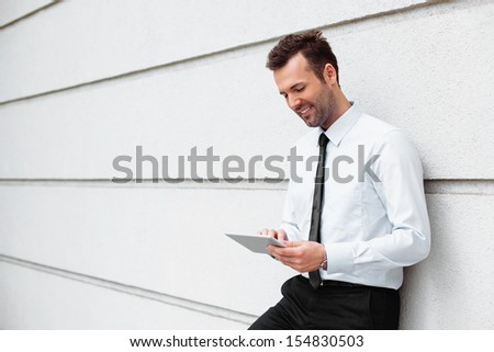 Relaxed businessman standing with digital tablet - stock photo