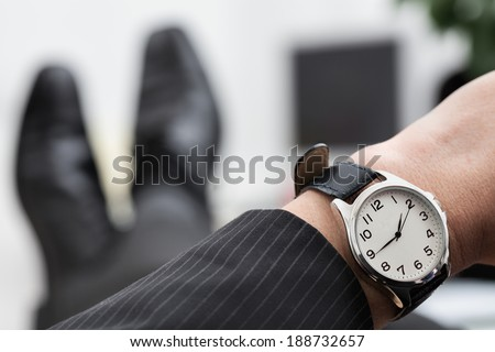 Relaxed businessman waiting to the end of work - stock photo