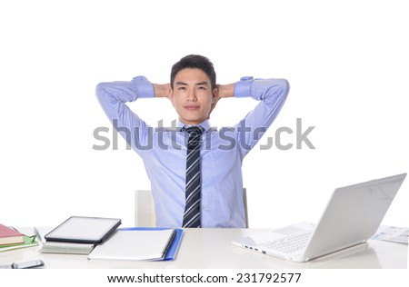 Relaxed businessman working with a laptop in his office - stock photo