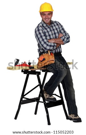 Relaxed carpenter next to a workbench - stock photo