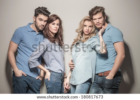 relaxed casual group of young fashion friends standing together against gray studio wall - stock photo