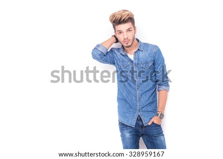 relaxed casual man with hand behind neck looks at the camera on white background - stock photo