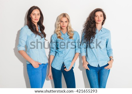relaxed casual women in jeans clothes standing with hands in pockets in studio - stock photo