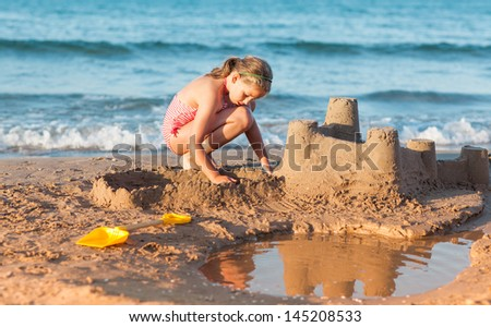 Relaxed child builds sandcastle on the beach - stock photo