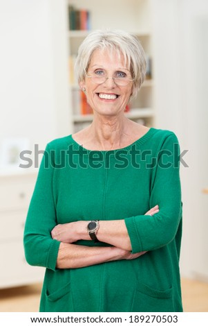 Relaxed confident beautiful senior woman standing wearing her reading glasses with folded arms and a lovely warm friendly smile - stock photo
