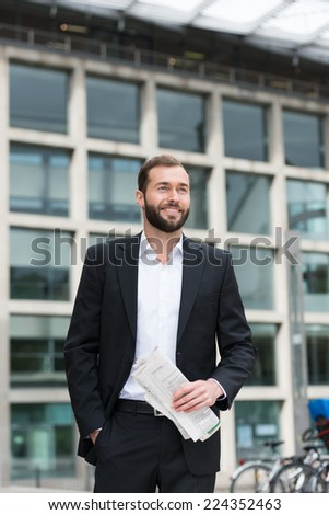 Relaxed confident businessman walking through town with a newspaper in his hand, low angle view against an office building - stock photo