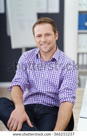 Relaxed confident young businessman in an informal office sitting back in his chair smiling at the camera - stock photo