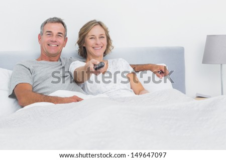 Relaxed couple watching tv in bed looking at camera at home in bedroom - stock photo
