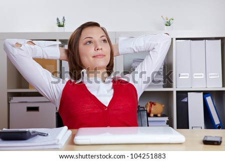 Relaxed female student at her desk leaning back - stock photo