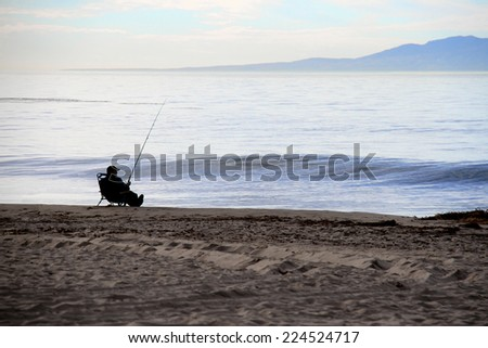 relaxed fisherman fishing on the ocean beach - stock photo