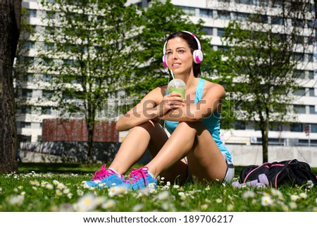 Relaxed fitness woman on a workout rest drinking detox smoothie on spring or summer. Beautiful fit girl taking a rest in city park. - stock photo