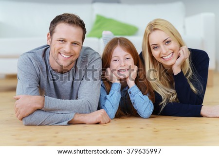 Relaxed friendly young family with a pretty daughter at home lying together on the wooden floor in the living room smiling happily at the camera - stock photo