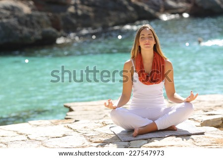 Relaxed girl doing yoga exercises on holidays in a tropical beach - stock photo