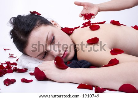 relaxed girl with rose petals - stock photo