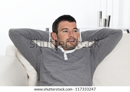 relaxed handsome man sitting on sofa at home - stock photo