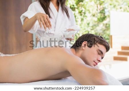 Relaxed handsome young man receiving treatment at spa center - stock photo