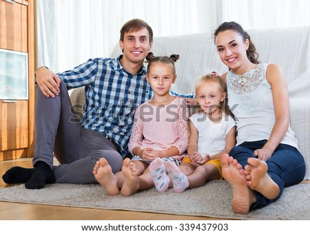 Relaxed happy family of four posing in the domestic interior  - stock photo