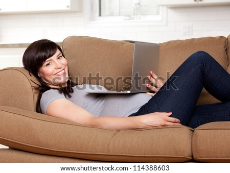 Relaxed happy pregnant woman sitting on sofa with laptop computer - stock photo