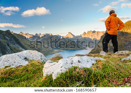 Relaxed hiker enjoys stunning views on fjords and mountain peaks of Lofoten islands, Norway - stock photo