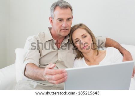 Relaxed loving couple using laptop on sofa at home - stock photo