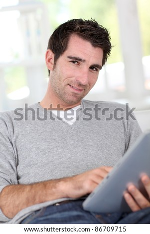 Relaxed man at home with electronic tablet - stock photo