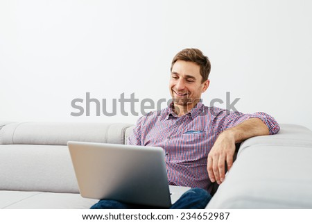 Relaxed man enjoying time with a laptop - stock photo