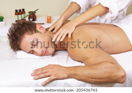 Relaxed man getting thai massage for his back in a day spa - stock photo