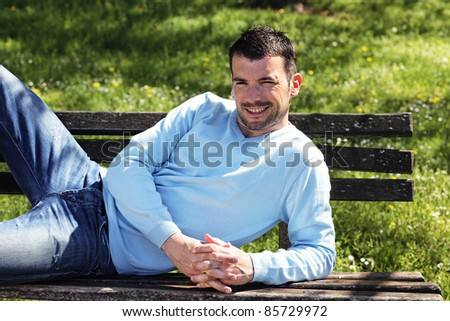 relaxed man on  a bench in a park in spring - stock photo