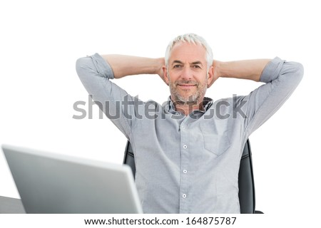Relaxed mature businessman sitting with hands behind head with laptop against white background - stock photo