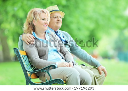 Relaxed mature couple sitting on a wooden bench in park  - stock photo
