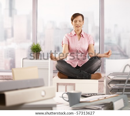 Relaxed office worker sitting on cabinet, doing yoga meditation with closed eyes, smiling.? - stock photo