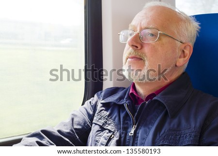 Relaxed old man sitting near the window in the carriage - stock photo