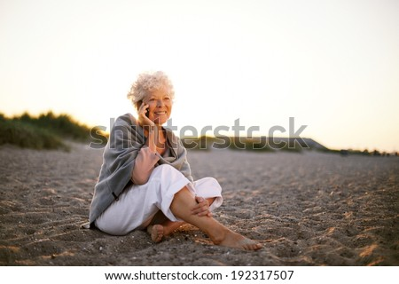 Relaxed retired woman wearing shawl sitting on sandy beach making a phone call. Old caucasian woman sitting on the beach looking at camera outdoors - stock photo