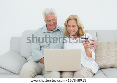 Relaxed senior couple doing online shopping through laptop and credit card on sofa in a house - stock photo