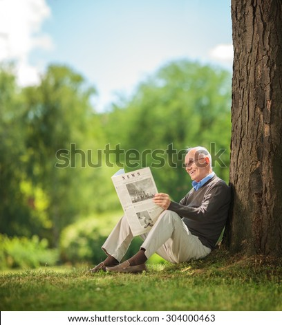 Relaxed senior gentleman reading a newspaper seated on the grass in a park.The newspaper is custom made, text is Latin and the pictures are my copyright. Additionally property release uploaded. - stock photo
