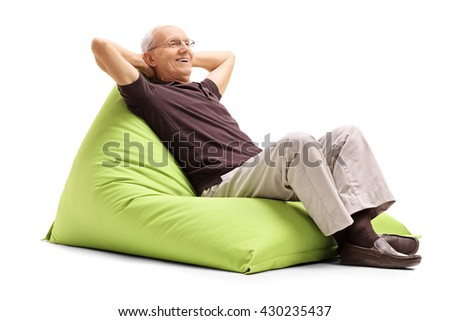 Relaxed senior gentleman sitting on a comfortable green beanbag isolated on white background - stock photo